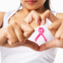 Heart framing on woman chest with pink badge to support breast c