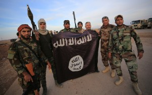 Iraqi Shi'ite fighters pose with an Islamic State flag which they pulled down on the front line in Jalawla, Diyala province, November 23, 2014. Iraqi forces said on Sunday they retook two towns north of Baghdad from Islamic State fighters, driving them from strongholds they had held for months and clearing a main road from the capital to Iran. Picture taken November 23, 2014. REUTERS/Stringer (IRAQ - Tags: CIVIL UNREST POLITICS CONFLICT MILITARY TPX IMAGES OF THE DAY) - RTR4FAVG